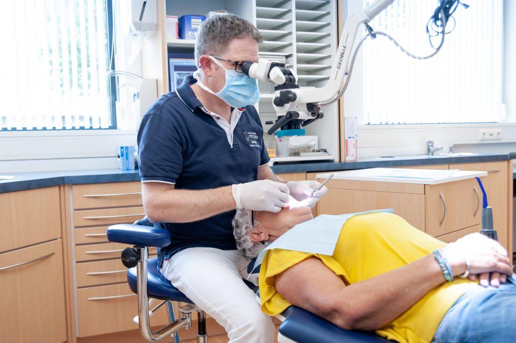 Tandarts Gertjan Postema aan het werk met een microscoop